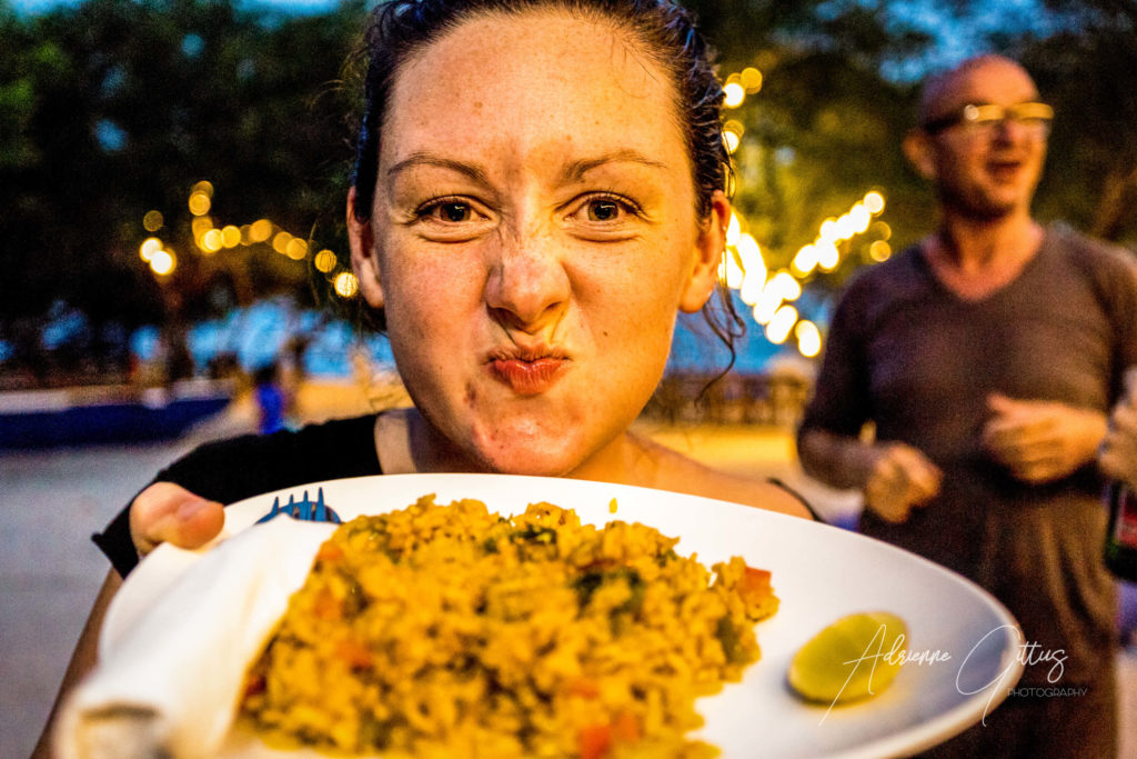 Girl with cheeky smile and plate full of delicious paella by the beach at night