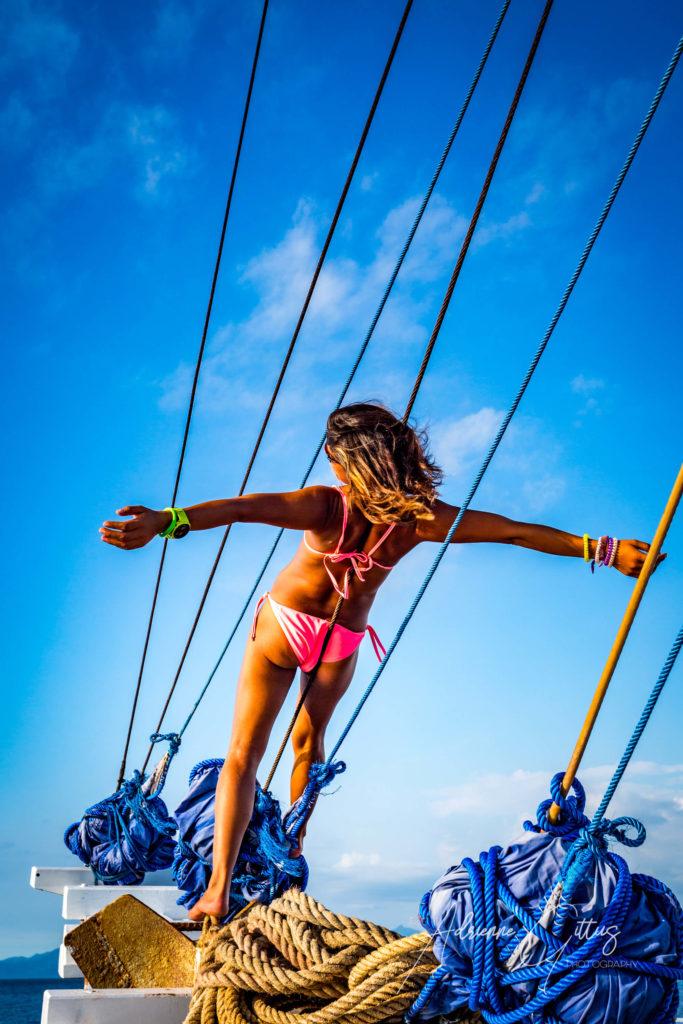 Beautiful girl in pink bikini on bow of a boat