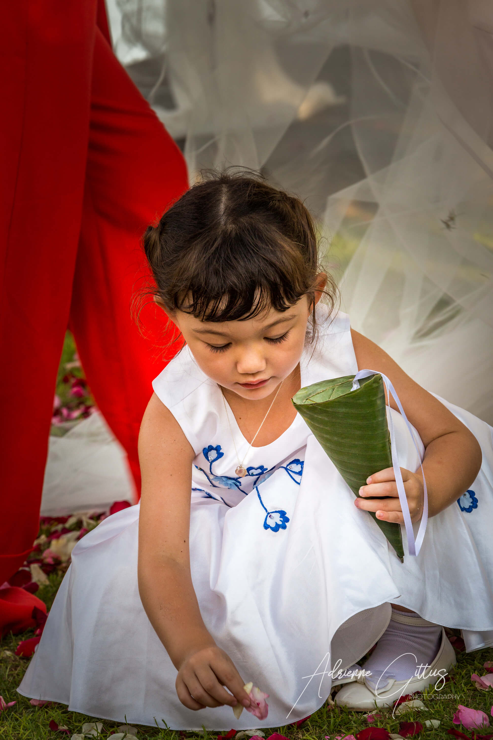 Portrait at a wedding of a flower girl picking up petals