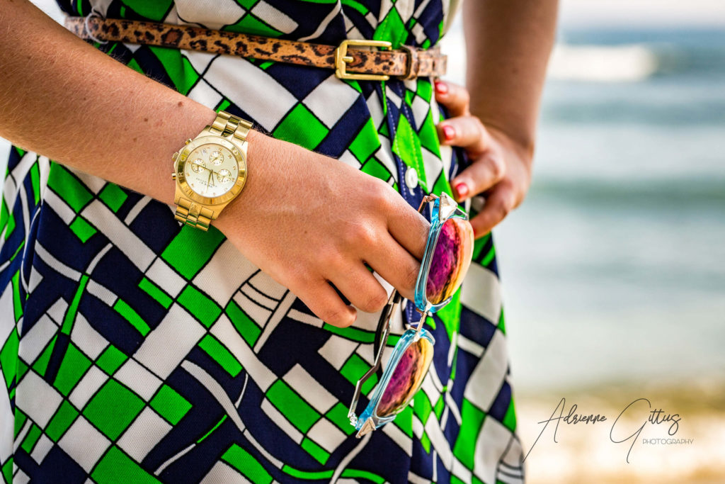Fashion closeup of womans hands with sunglasses watch and belt in a green dress