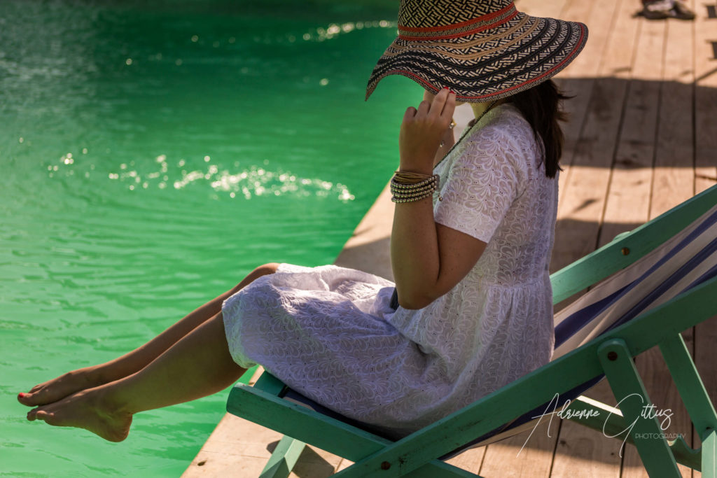 Fashion image of woman in a white sundress and floppy sunhat in chair by a pool