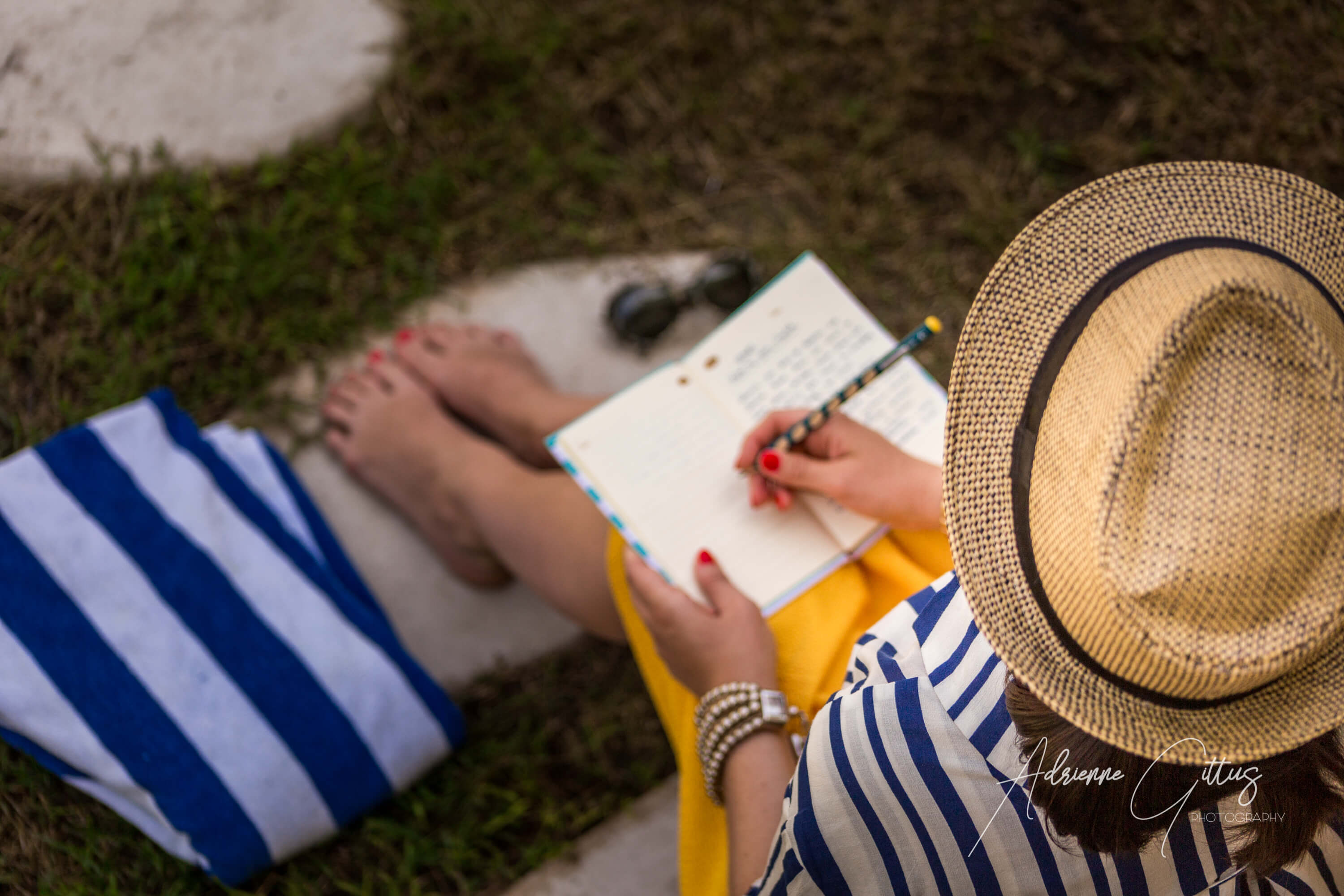 Looking over shoulder of woman with diary in straw hat fashion