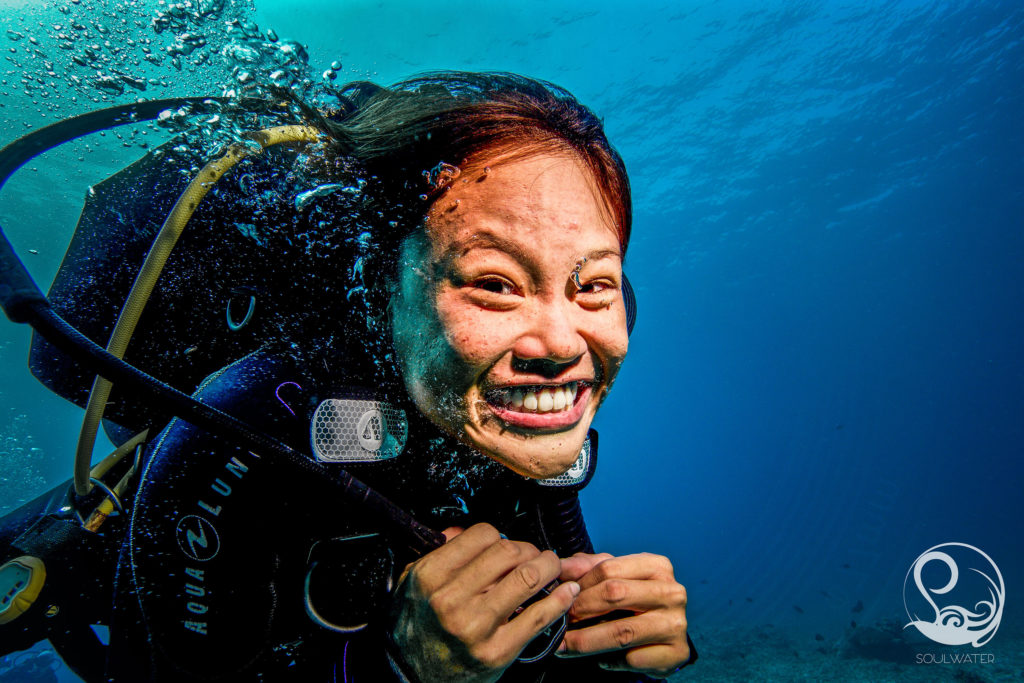 Excited scuba diver smiling underwater