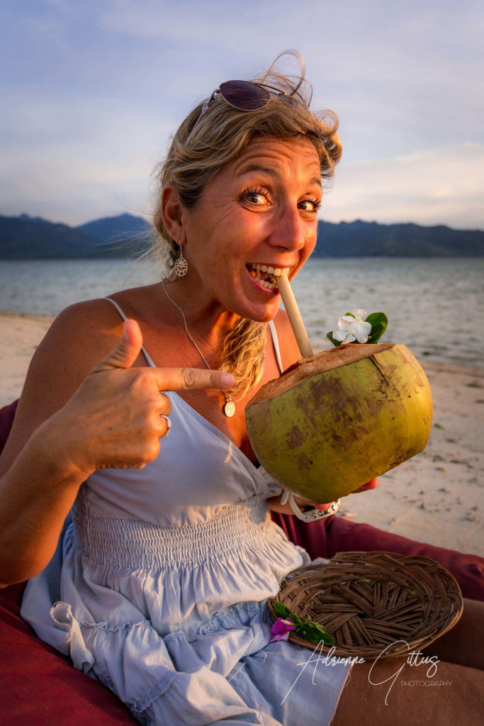 Beautiful woman drinking a coconut on the beach at sunset