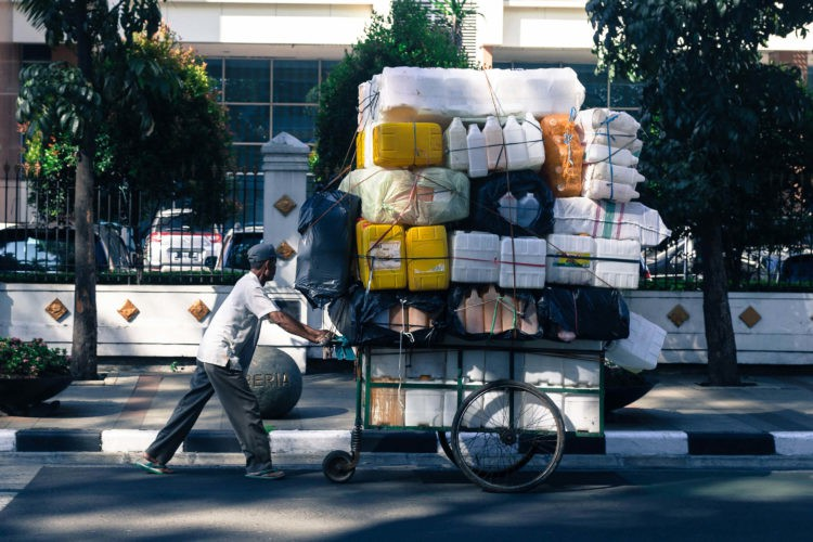 Man pushing cart loaded with plastic containers in Indonesia