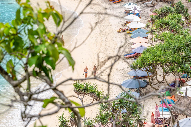 Quiet white sandy beach with umbrellas and beach shack restaurants, Atuh Beach, Nusa Penida, Bali, Indonesia
