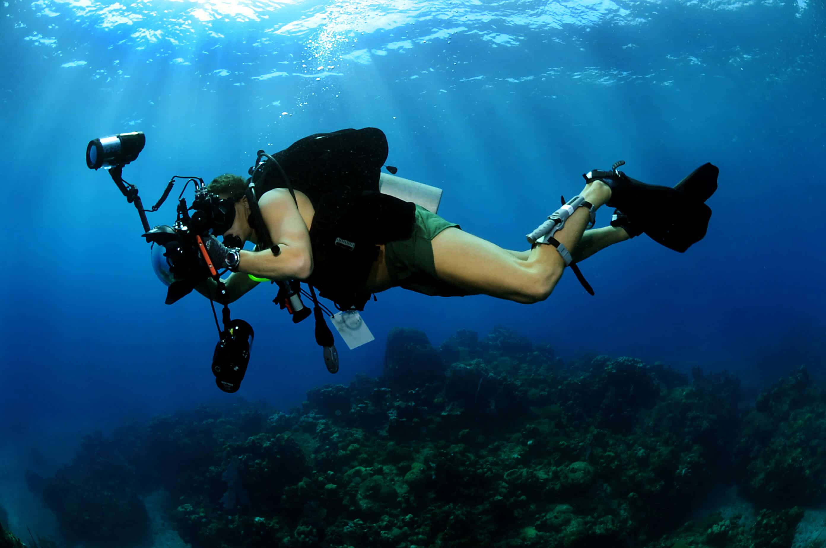 diver with a large camera in good working position and showing good buoyancy