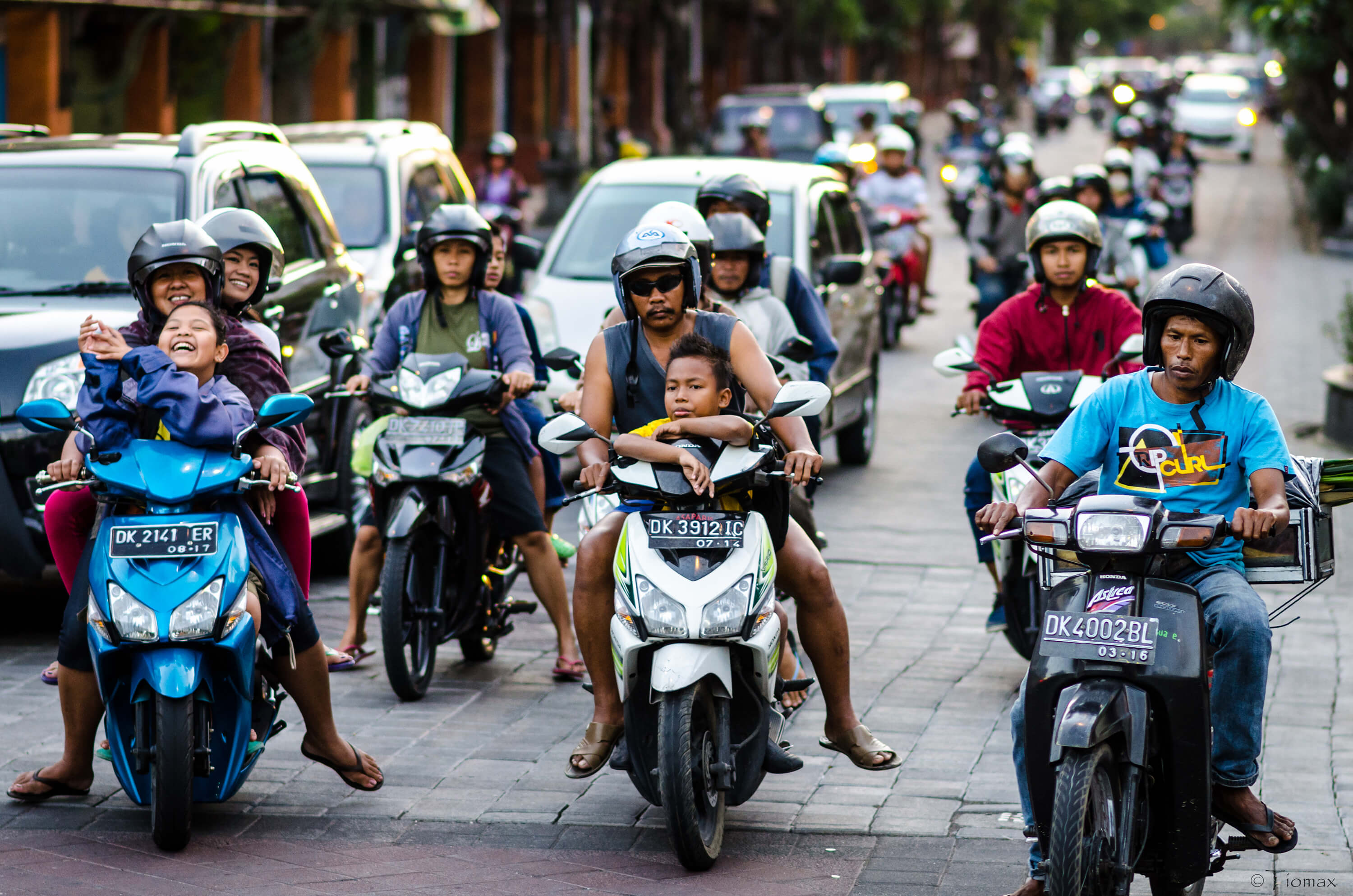 Motor bikes in congested traffic, with small children on bikes with no helmet, Indonesia