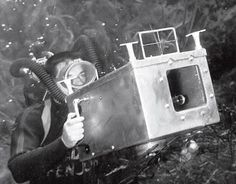 Black and white image of Mozert Bruce, Underwater photography pioneer, with homemade camera housing