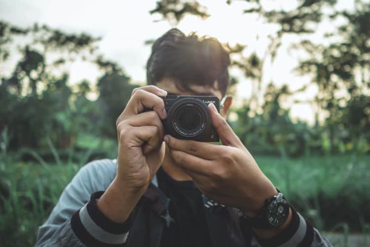 Young man holding camera to his eye in beautiful llush green background